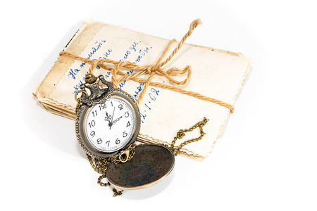 Old photographs and round pocket watch on a white background Zdjęcie Seryjne