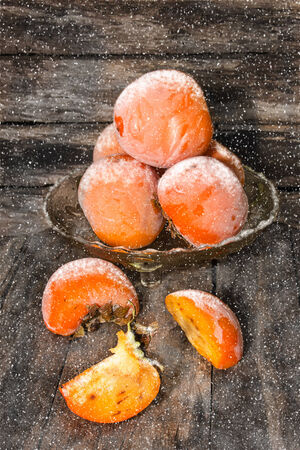thawed: Ripe fruits are thawed in a vase on the wooden background