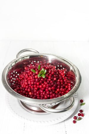 macerated: Soaked cowberry in a metal colander on a light background
