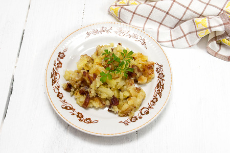 calory: Fried potatoes with parsley on the plate on a wooden table