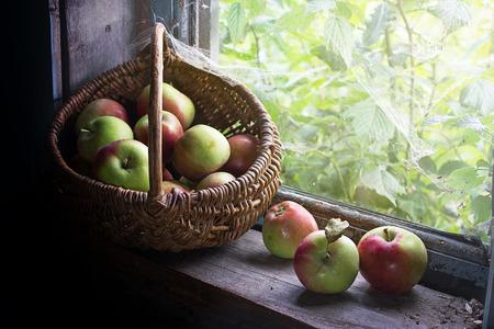 windowsill: Lighted sunlight basket with apples on the windowsill