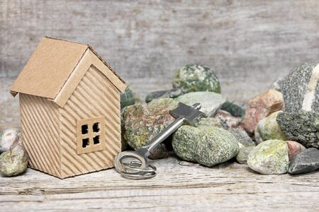 privatization: house, key and stones on wooden background
