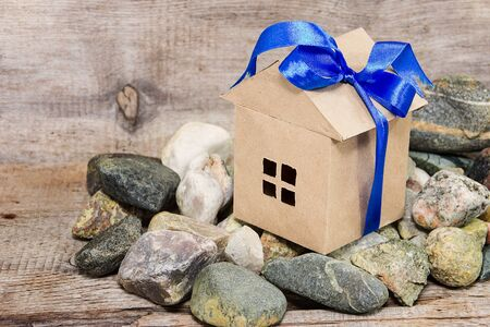 Paper house tied with a blue bow on plank background