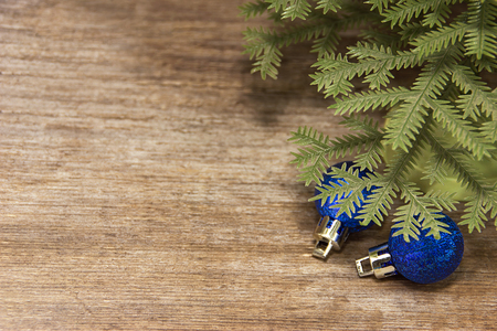 purchased: Blue Christmas toys lie under the fir branches on plank background