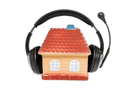 decibels: Ceramic house with headphones on white background Stock Photo