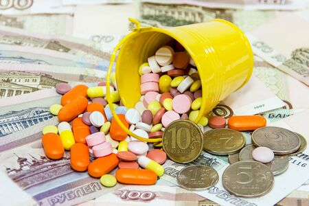 bucket of money: Many different pills spilled from a bucket on a background of Russian money