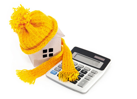 The costs of home insulation. House in a hat with a scarf and a calculator Stock Photo
