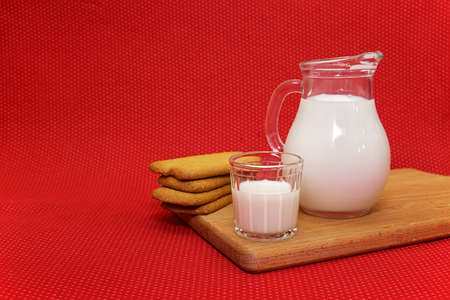 ewer: Milk in a ewer and a glass on a red background