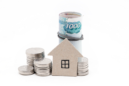 Cardboard house, coins and bills on a white background Stock Photo