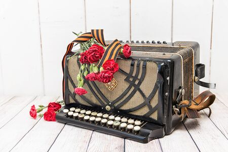 Accordion, red carnations and St. George ribbon. Victory Day. May 9