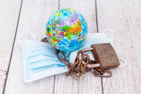 Medical mask, rusty chain with a lock and a globe. Fighting the global epidemic