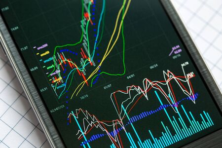 Data analyzing in stock exchange market: the charts and quotes on smartphone display.