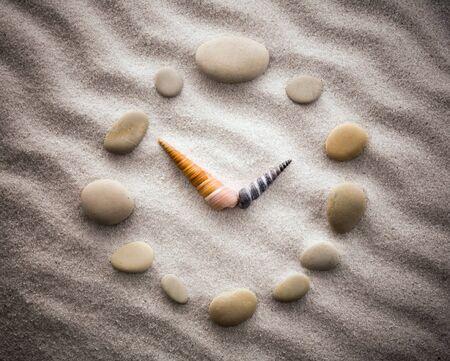 despacio: Reloj estilizado reloj piedrecitas y conchas flechas en la arena para la concentración y la relajación para la armonía y el equilibrio en la simplicidad pura - lente macro disparo