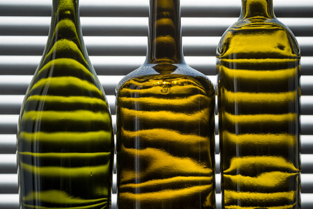 three empty bottles of wine on the background of blinds backlit