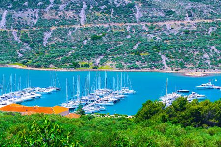 Wonderful romantic summer afternoon landscape panorama coastline Adriatic sea. Boats and yachts in harbor at magical clear transparent azure water. Olive trees grove. Cres island. Croatia. Europe.
