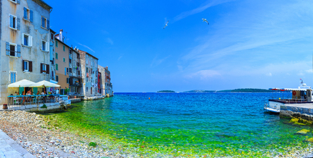 Wonderful romantic old town at Adriatic sea. Old houses in the harbor azure-turquoise crystal-clear water at magical summer. Blurred-unrecognizable faces. Rovinj. Istria. Croatia. Europe. Stock Photo