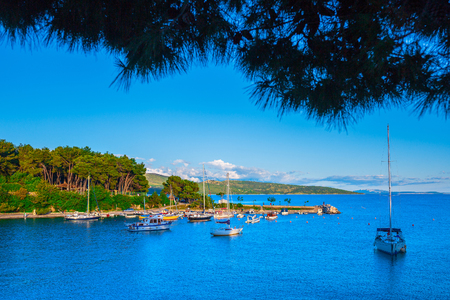 Wonderful romantic summer landscape panorama coastline sea. Boats and yachts in harbor at cristal clear azure water. Green trees at the edge of the coast.