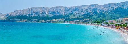 Wonderful romantic summer afternoon seascape Adriatic island. Big, long, clean - pebbly Vela Plaža Beach in harbor at cristal clear blue water. Unrecognizable person - blurred faces. Baska on the island of Krk. Croatia. Europe. Stock Photo