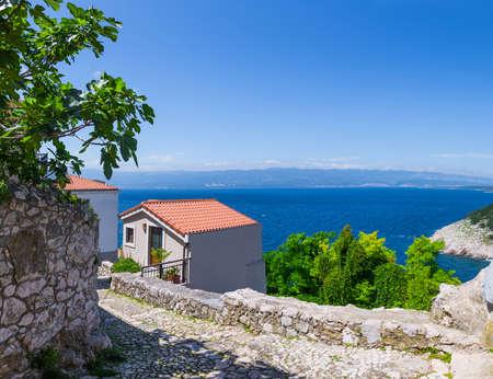 Wonderful romantic summer afternoon landscape coastline Adriatic sea. Narrow streets paved with stone. Krk island. Croatia. Europe. Stock Photo