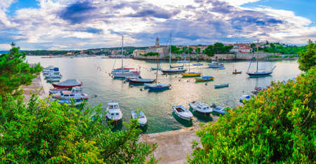 Wonderful romantic summer evening landscape panorama coastline Adriatic sea. Boats and yachts in harbor at cristal clear azure water. Old town of Krk on the island of Krk. Croatia. Europe.
