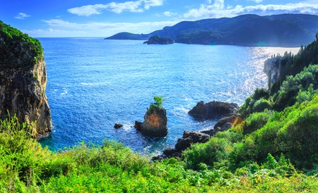 Beautiful summer panoramic seascape. View of the coastline into the sea bays with crystal clear azure water. Lonely rock with a tree on top. A small tree on top. Paleokastrica. Corfu. Greece.