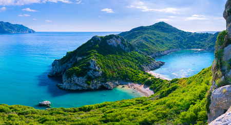 Beautiful summertime panoramic seascape. View of the cliff into the crystal clear azure sea bay and distant islands. Unique secluded beach. Agios Stefanos cape. Afionas. Corfu. Greece. Stock Photo