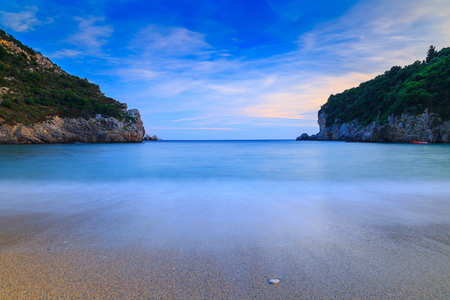 Long exposure landscape of Paleokastritsa famous sand beach in close bay on Corfu island at dusk, Ionian archipelago, Greece. Stock Photo