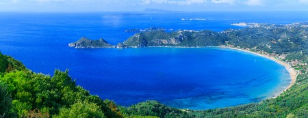 Beautiful summertime panoramic seascape. View of the cliff into the crystal clear azure sea bay and distant islands. Agios Stefanos cape. Afionas. Corfu. Greece. Stock Photo