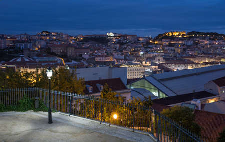 Evening view of old town Lisbon and Sao Jorge Castle from Garden of San Pedro de Alcantara, the capital and the largest city of Portugal.
