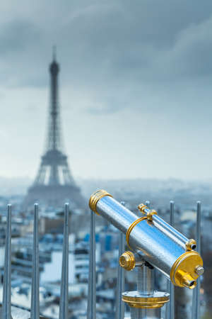 Touristic telescope or spyglass in rain drops directed towards the Eiffel Tower. Paris. France.