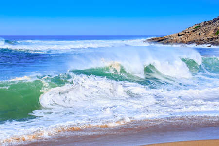 A huge waves on the ocean coast in a shine bright light at sunny day. Wonderful romantic seascape of ocean coastline.