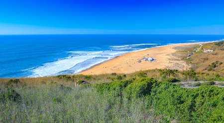 Awesome aerial sunny seascape coastline of Atlantic ocean. View North Beach (Praia do Norte). Most famous place of giant breaking waves for surfers from around the world. Nazare, Portugal. Foto de archivo