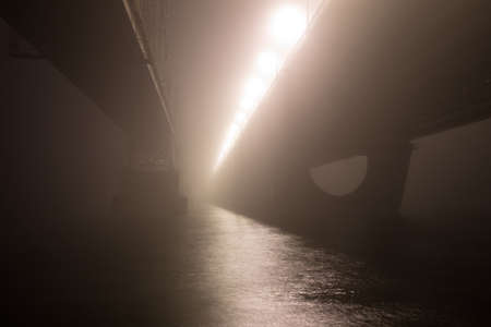 A mysterious evening fog above the river in big city. Bridge in the mist, cold weather scenery. Soft, blurry, misty look. Colorful, mystic industrial cityscape.