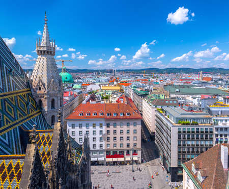 Aerial panoramic cityscape view of austrian capital city of Vienna from the Northern tower Saint Stephen's cathedral. Summertime sunshine day, small cumulus clouds in the blue sky.