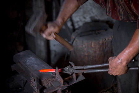 Blacksmith's hands at work. In one hand a hammer, in the other a workpiece of hot metal. Master methodically hammer hits the anvil. An example of the hard work of ancient crafts. Foto de archivo