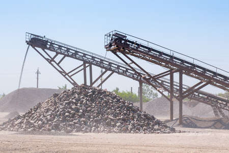 Crushing machinery, cone type rock crusher, conveying crushed granite gravel stone in a quarry open pit mining. Processing plant for crushed stone and gravel. Mining and Quarry mining equipment. Banque d'images
