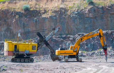 A large tracked excavator and pneumatic hammer in a quarry open pit mining of granite stone. Process production stone and gravel. Quarry mining equipment.