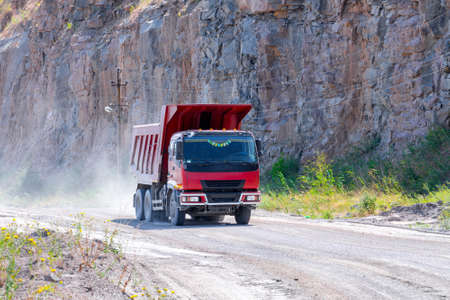 A dump truck loaded mined granite in a quarry open pit mining of granite stone. Process production stone and gravel. Quarry mining equipment.