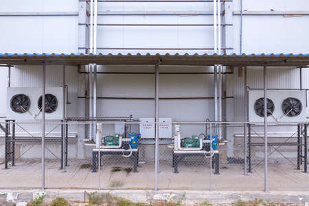External infrastructure of the industrial refrigeration installation at a large industrial site. Air and liquid substance pipelines inlet exhaust, compressors, and fans. Archivio Fotografico
