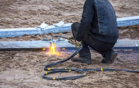 A worker cut steel beams using propane-oxygen torch. Oxy-fuel cutting.