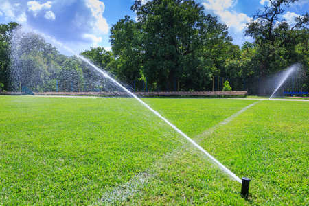 Automatic lawn grass watering system at the stadium. A football, soccer field in a small provincial town. Underground sprinklers spray jets water. Archivio Fotografico