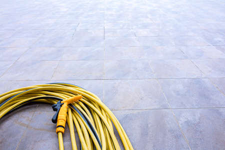 Yellow garden hose for watering lying in a floor curled in the corner. Reklamní fotografie