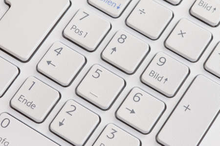 White computer keyboard in German language. Numpad. Selective focus with shallow depth of field.