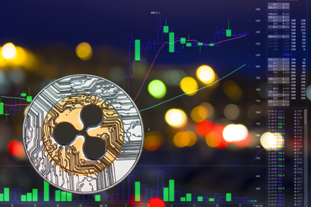 Coin cryptocurrency Ripple on night city background and chart. Stock Photo
