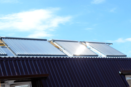 Vacuum collectors- solar water heating system on roof of the house. Stockfoto