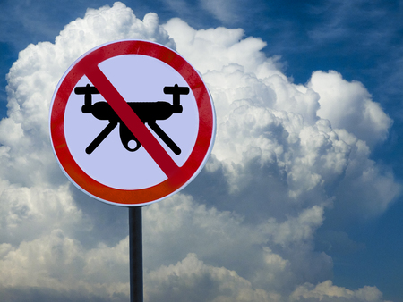 Round sign banning drones on sky and clouds background.