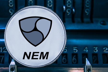 Coin cryptocurrency NEM and numbers of the arithmometer. The concept of production or rate of xem. Stock Photo
