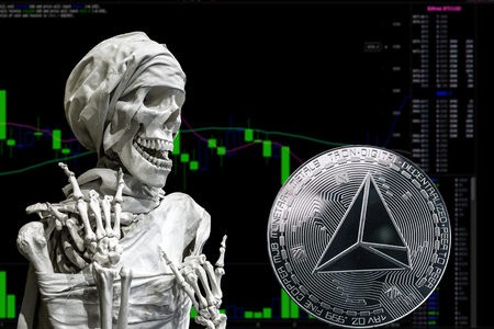Coin cryptocurrency Tron and skeletonon a background chart.
