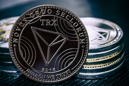The coin cryptocurrency Tron on the background of a stack of coins. Banco de Imagens