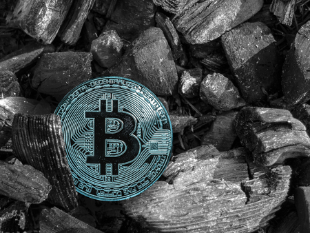 The cryptocurrency Bitcoin coin lies on coal. Mining and Energy for mining.
